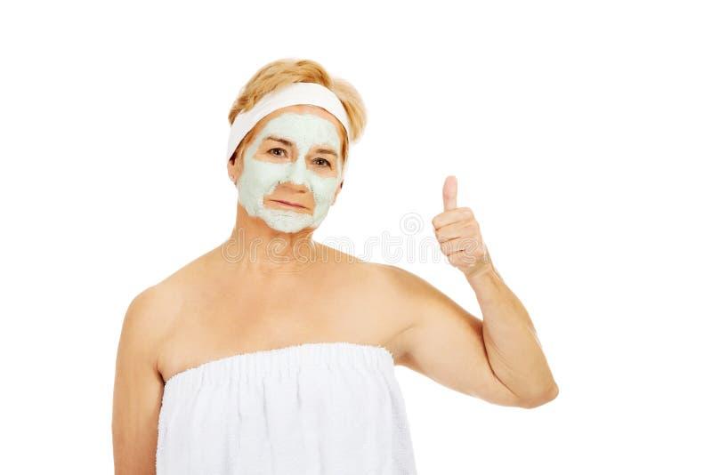Женщина улыбки пожилая с лицевой маской показывает большой палец руки вверх стоковая фотография rf