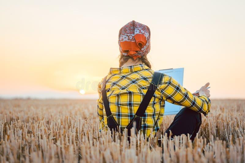 Женщина фермера высчитывая выход сбора после длинного дня стоковая фотография