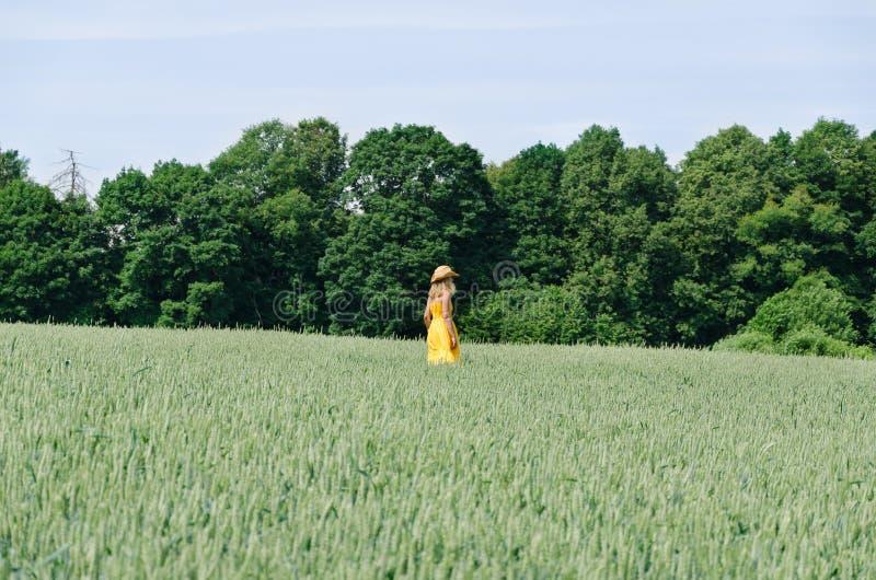 Женщина фермера в желтом пшеничном поле прогулки платья стоковая фотография