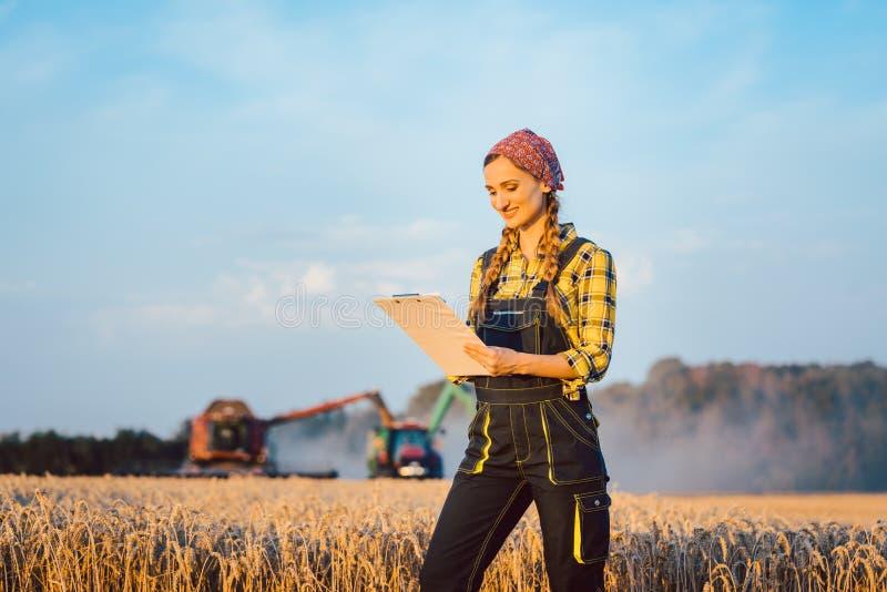 Женщина фермера с доской сзажимом для бумаги на поле, сборе идя дальше стоковое изображение