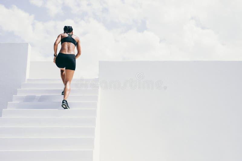 Женщина фитнеса бежать вверх лестницы здания стоковые фото