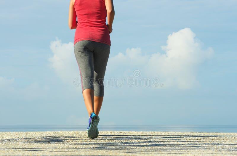 Женщина фитнеса бежать в побережье на восходе солнца стоковая фотография