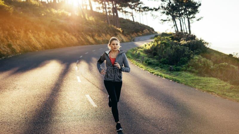 Женщина фитнеса бежать на пустой дороге с пирофакелом солнца на заднем плане Женщина в носке фитнеса бежать вниз с холмистой доро стоковое изображение