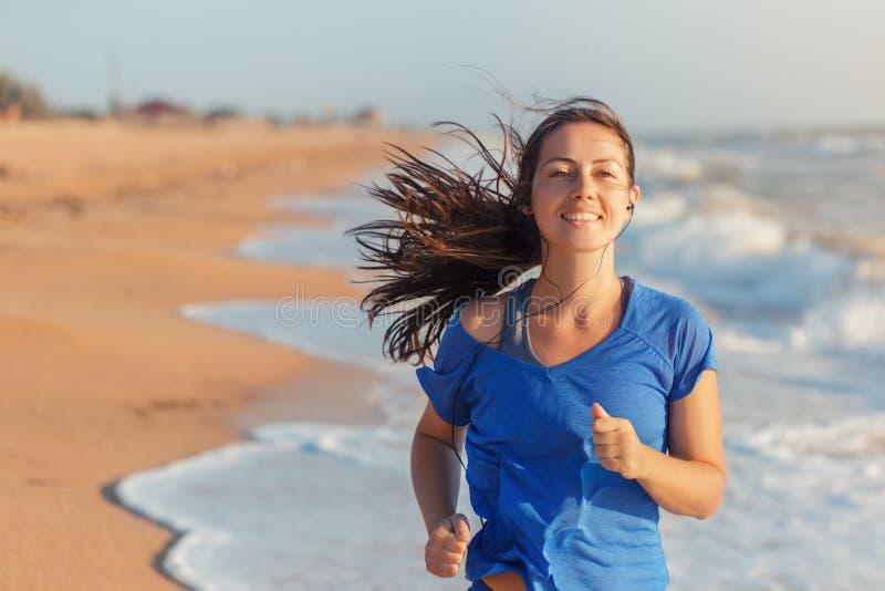 Женщина фитнеса бежать на пляже стоковое изображение rf