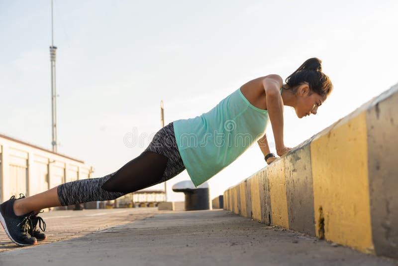 Женщина фитнеса делать нажимает поднимает образ жизни внешнего спорта концепции взгляда со стороны вечера лета разминки тренировк стоковые изображения rf