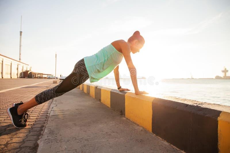 Женщина фитнеса делать нажимает поднимает образ жизни внешнего спорта концепции взгляда со стороны вечера лета разминки тренировк стоковое изображение rf