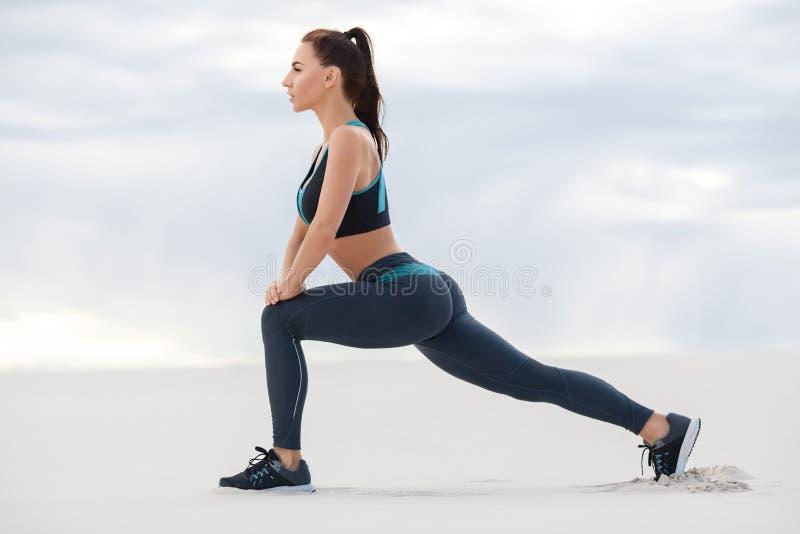 Женщина фитнеса делая выпады работает для тренировки разминки мышцы ноги, внешний Активная девушка делая передний вперед один вып стоковая фотография rf