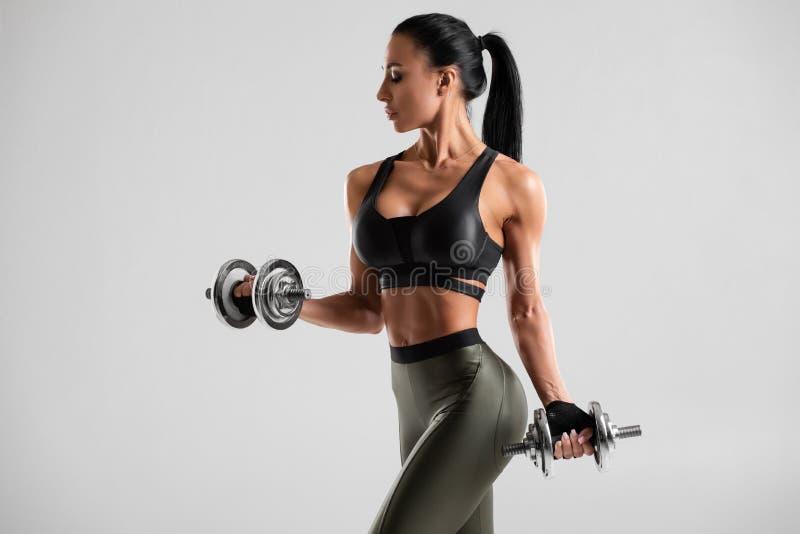 Женщина фитнеса делая тренировку для бицепса на серой предпосылке Мышечная разминка женщины с гантелями стоковые изображения