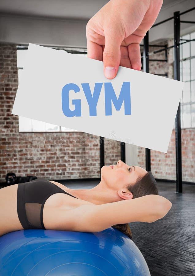 Женщина фитнеса лежа над шариком тренировки при рука держа текст с плакатом стоковая фотография