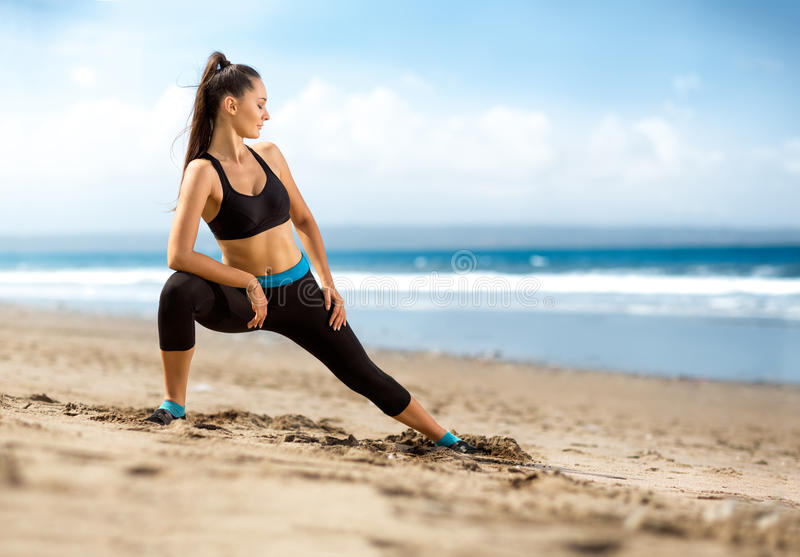 Женщина фитнеса делая разминку на пляже стоковое изображение