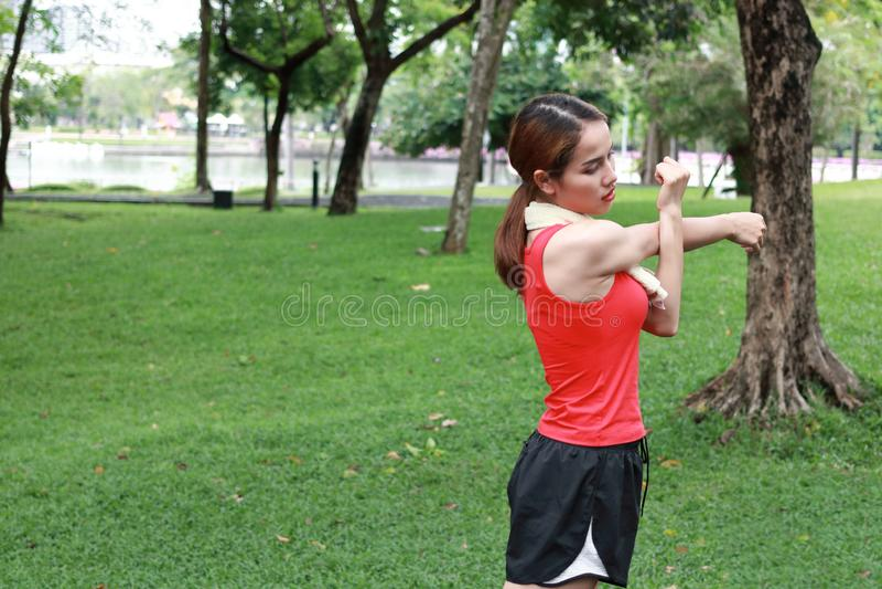 Женщина фитнеса молодая азиатская протягивая ее руки перед бегом в парке Разминка и концепция тренировки стоковые фотографии rf