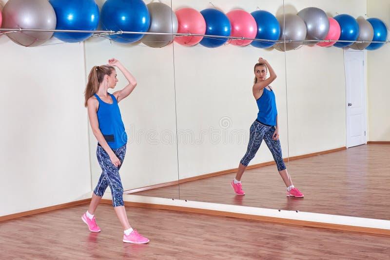 Женщина фитнеса, протягивая ее тело, перед разминкой, перед зеркалом на спортзале скопируйте космос стоковое изображение