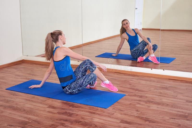 Женщина фитнеса, протягивая ее тело, перед разминкой, перед зеркалом на спортзале стоковые изображения