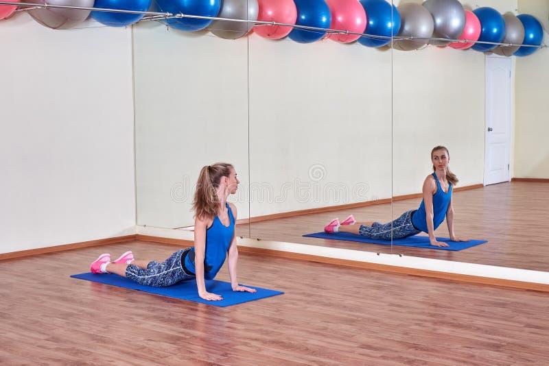 Женщина фитнеса, протягивая ее тело, перед разминкой, перед зеркалом на спортзале скопируйте космос стоковая фотография rf