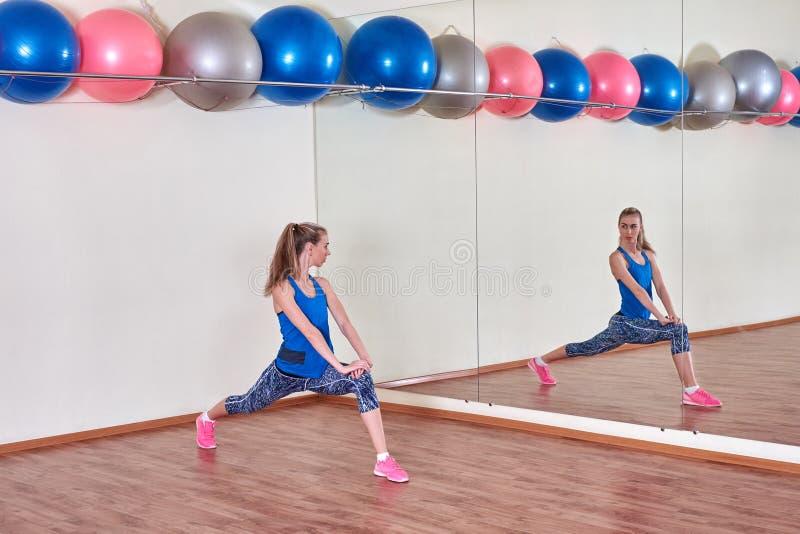 Женщина фитнеса, протягивая ее тело, перед разминкой, перед зеркалом на спортзале скопируйте космос стоковое фото