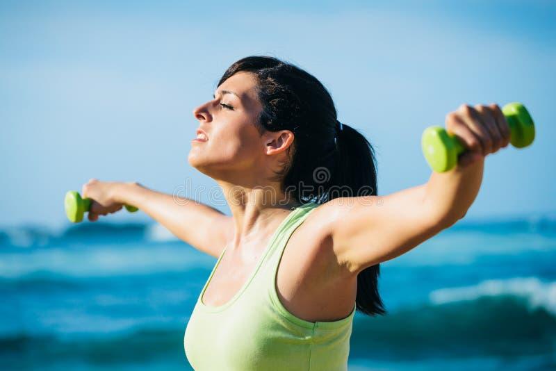Женщина фитнеса разрабатывая с гантелями внешними стоковое фото