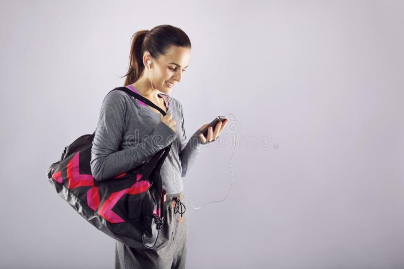 Женщина фитнеса с музыкой сумки спортзала слушая стоковая фотография