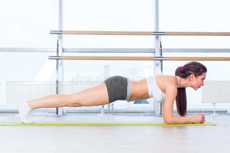 Женщина фитнеса тренировки делая тренировку ядра планки разрабатывая для задних pilates концепции позвоночника и позиции резвится стоковые изображения