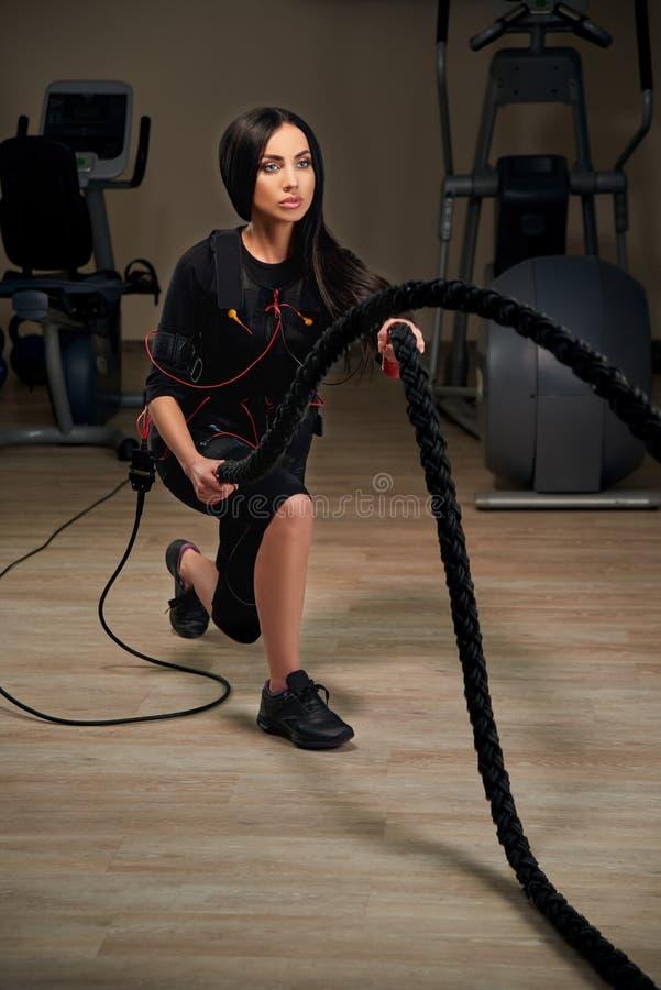 Женщина фитнеса EMS брюнет делая тренировку crossfit используя веревочку g стоковое фото rf