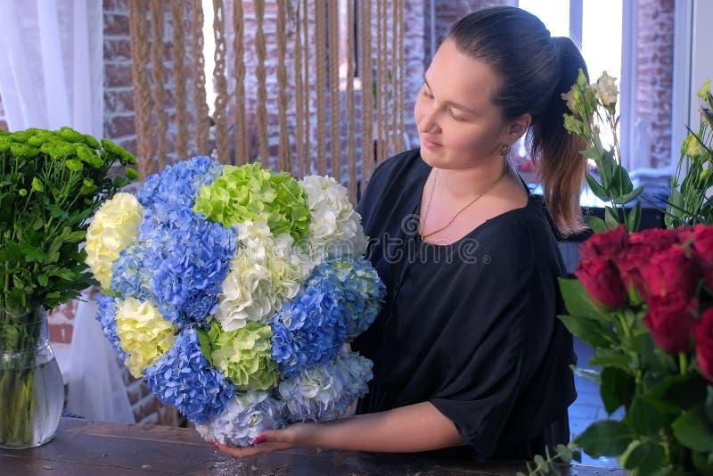 Женщина флориста с огромным сделанным букетом цветков гортензии во флористическом магазине стоковые изображения rf