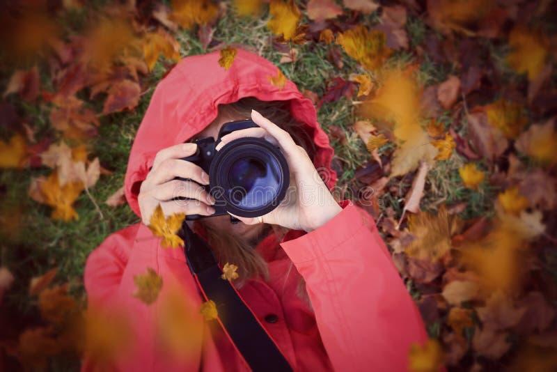 Женщина фокусируя камеру кладя в листья осени стоковая фотография