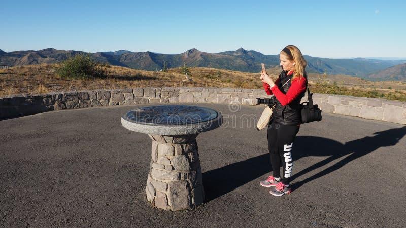 Женщина фотографируя дирекционный памятник на памятнике Сент-Хеленс национальном вулканическом стоковое изображение rf