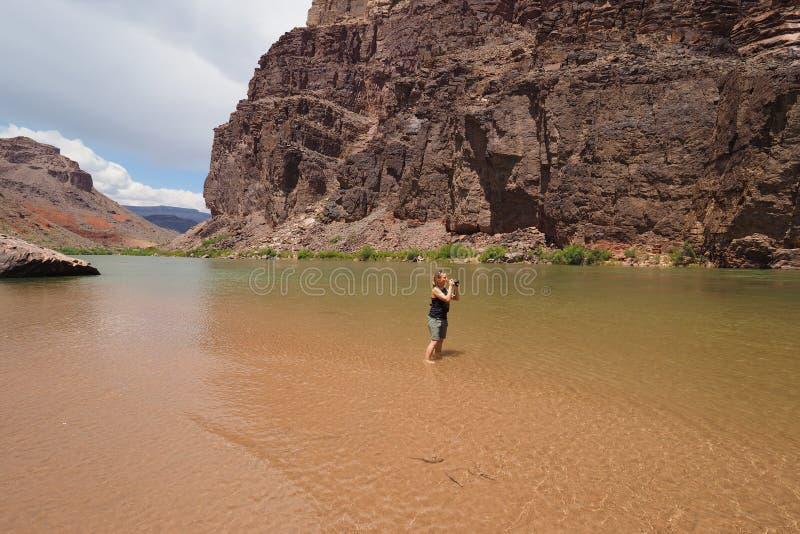 Женщина фотографируя реку Colrado и внутренний каньон в гранд-каньоне стоковое фото