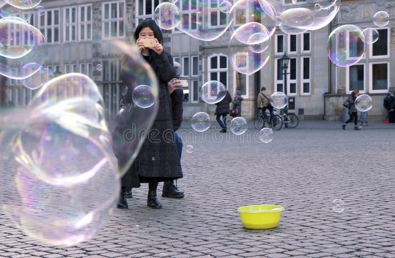 Женщина фотографируя толпу пузырей мыла в Бремене Германии стоковые фотографии rf