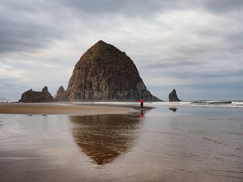Женщина фотографируя утес стога сена на пляже карамболя, Орегоне стоковое фото