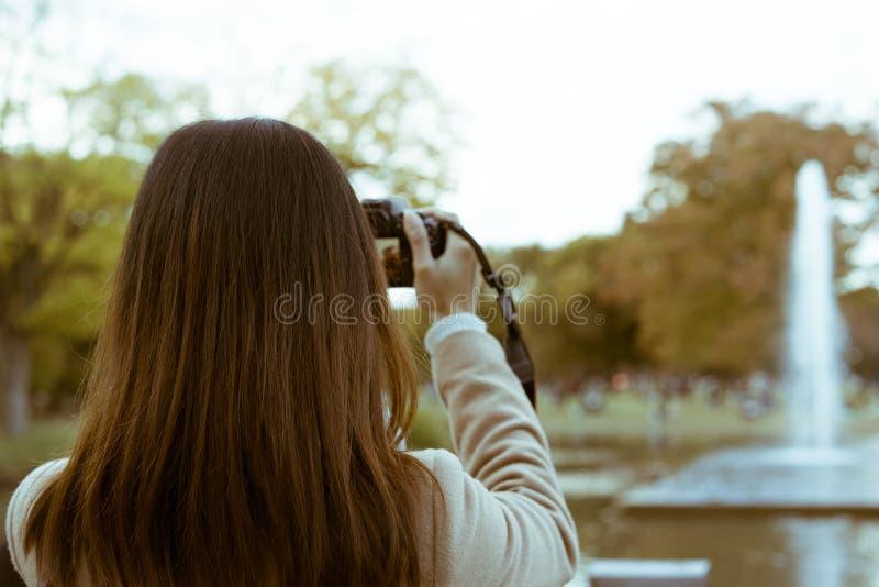 Женщина фотографируя фонтан в парке Yoyogi во время осени в токио, Японии стоковое изображение