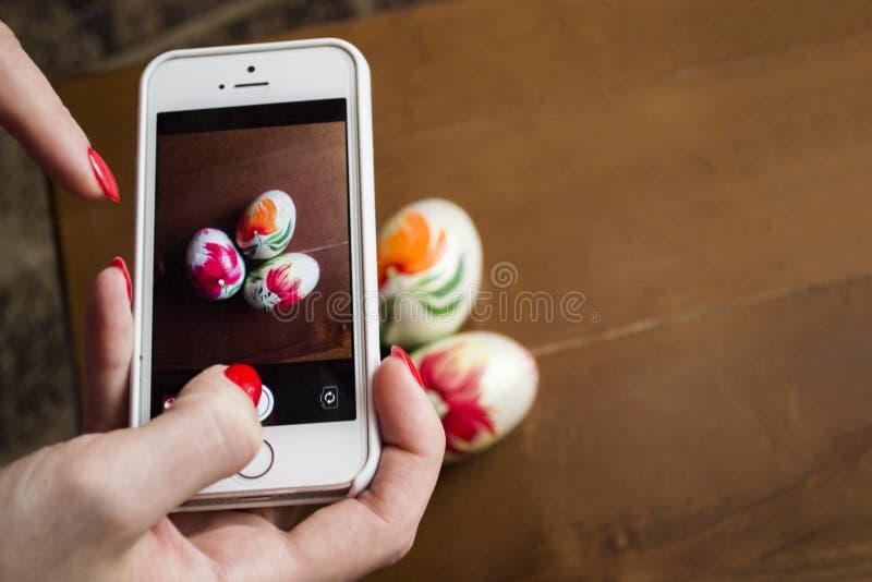Женщина фотографируя 3 handmade пасхального яйца на деревянной плате стоковое изображение