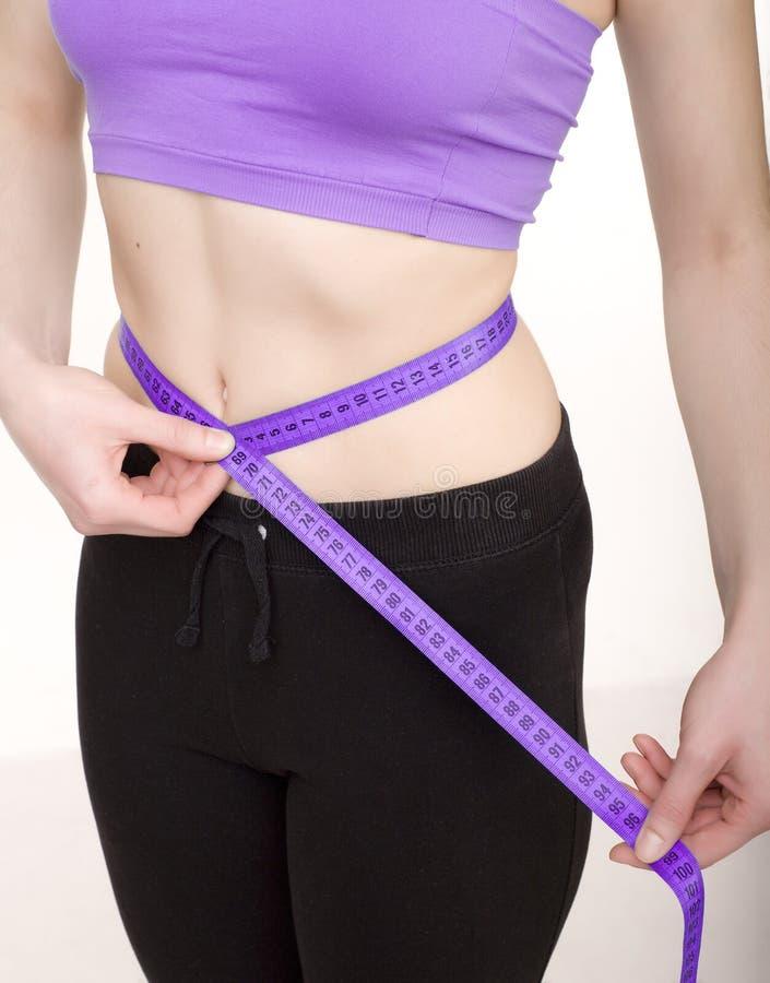 Женщина фото запаса измеряя ее тонкое тело изолированное на белой предпосылке стоковые фотографии rf