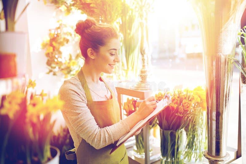 Женщина флориста с доской сзажимом для бумаги на цветочном магазине стоковое фото