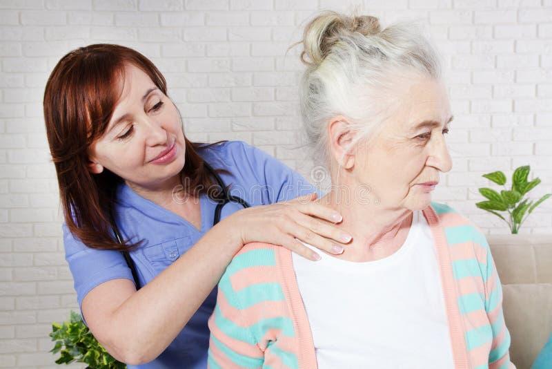 Женщина-хиропрактик, наблюдающая за пожилой женщиной с болью в шее в медицинском кабинете или спальне Лечение престарелых стоковое изображение