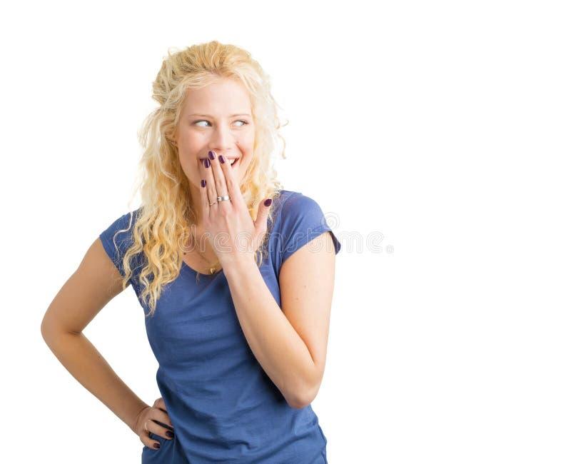 Женщина хихикая с ее рукой перед ртом стоковое изображение