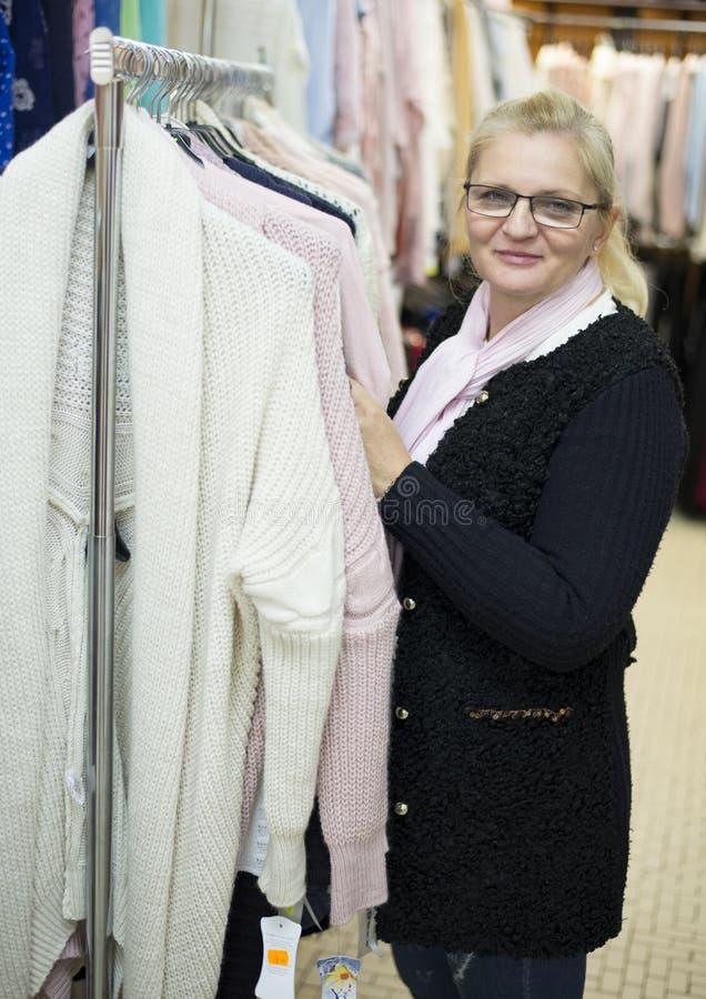 Женщина ходя по магазинам одежды в магазине ткани на продаже стоковые изображения