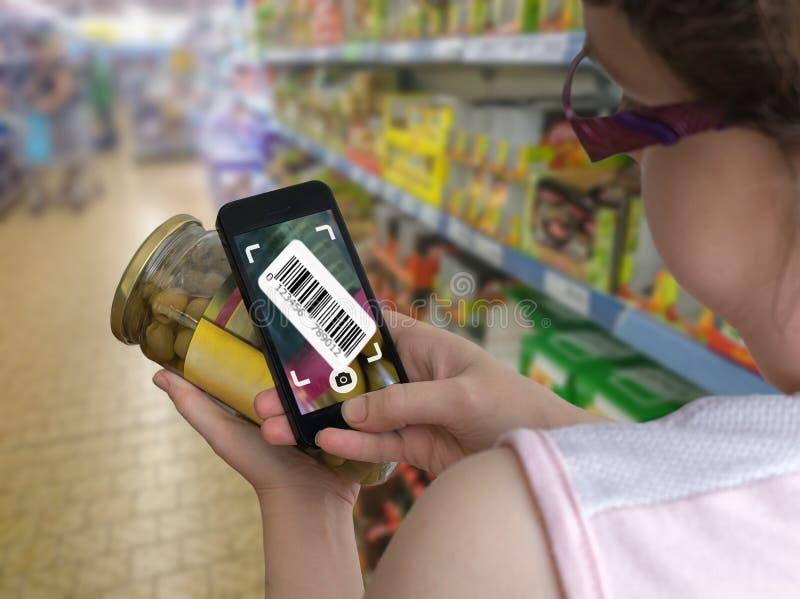 Женщина ходит по магазинам в супермаркете и просматривая штрихкоде с smartphone в гастрономе стоковое изображение rf