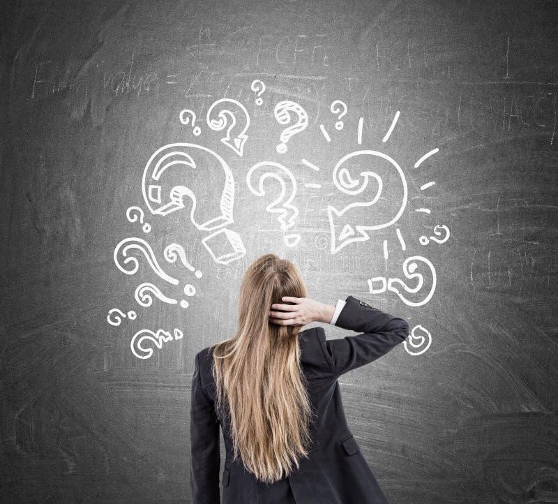 Женщина царапая голову и вопросительные знаки на классн классном стоковое фото rf