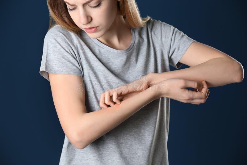 Женщина царапая предплечье на предпосылке цвета Симптом аллергии стоковое изображение