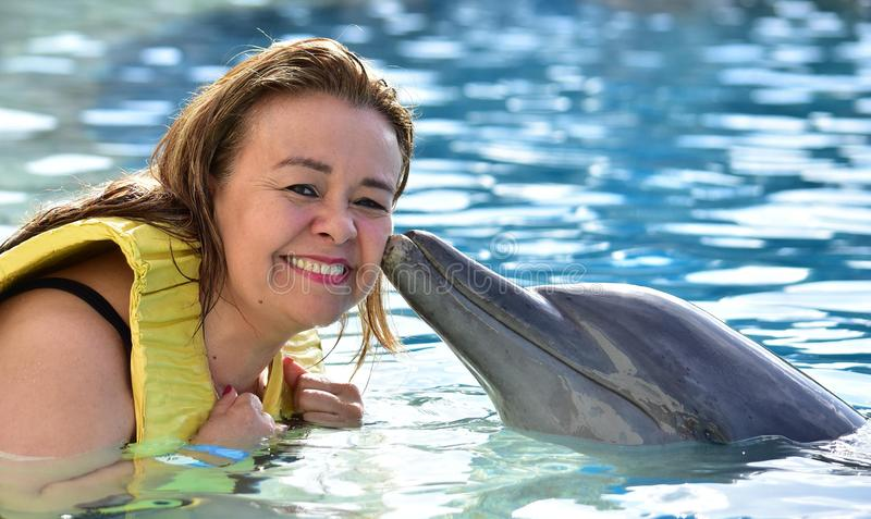 Женщина целуя дельфина в бассейне стоковые изображения rf