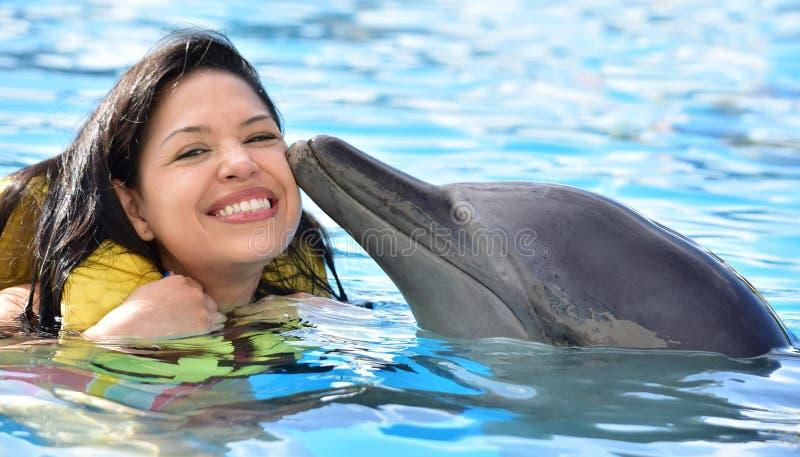 Женщина целуя дельфина в бассейне стоковое фото rf