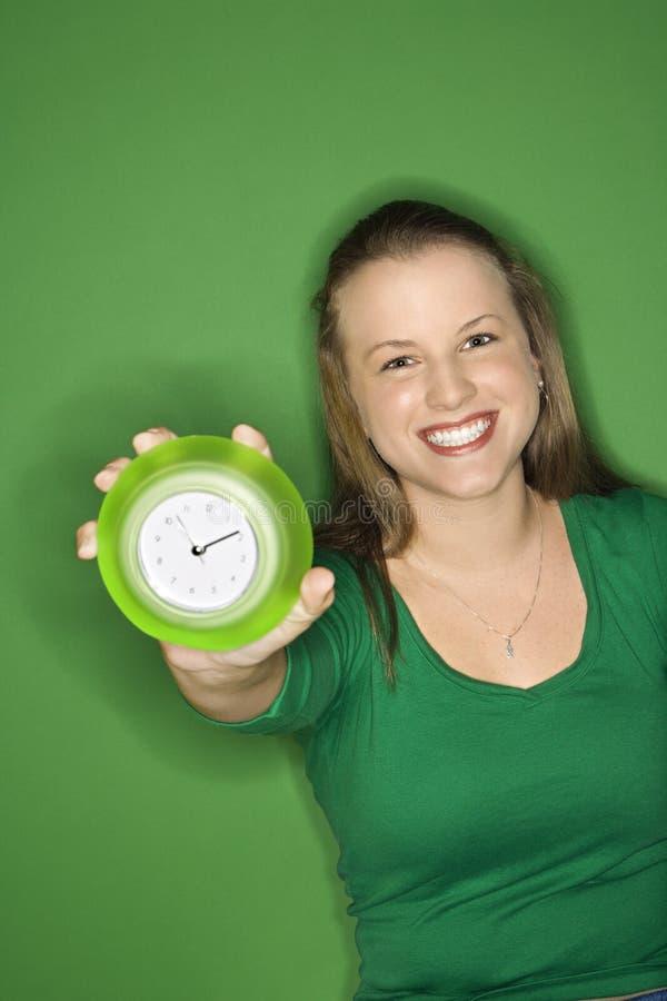 женщина часов держа вне стоковое фото