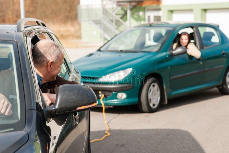 Женщина человека помогая путем вытягивать ее автомобиль стоковая фотография rf