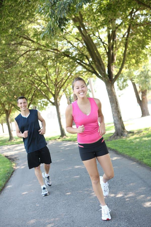 женщина человека привлекательных пар jogging стоковое изображение