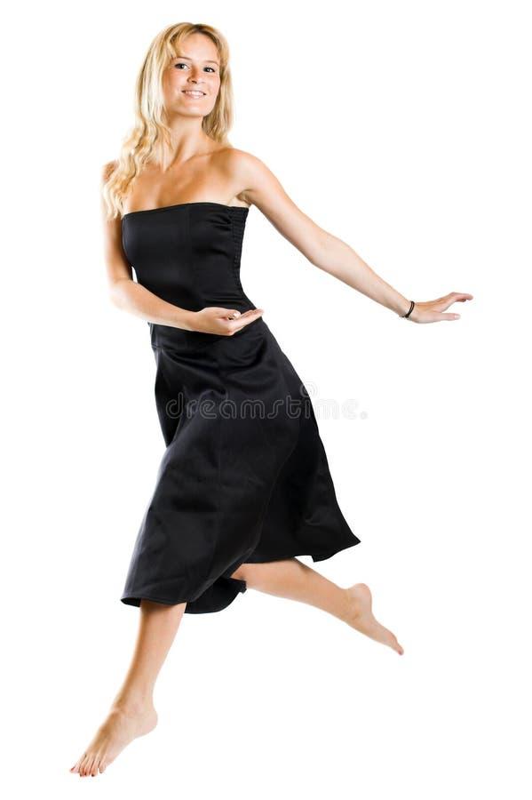 женщина черного платья скача стоковое изображение rf