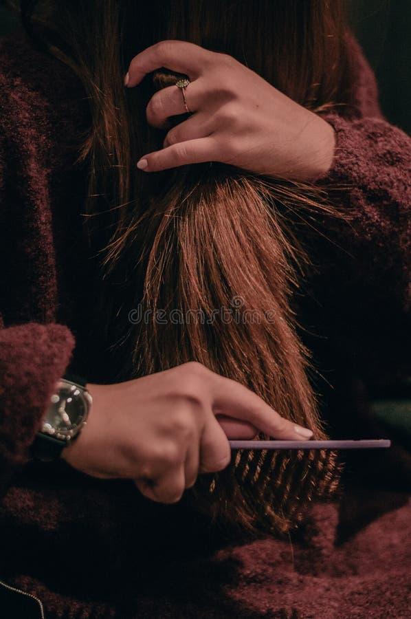 Женщина чистя ее волосы щеткой в утре outdoors стоковое фото