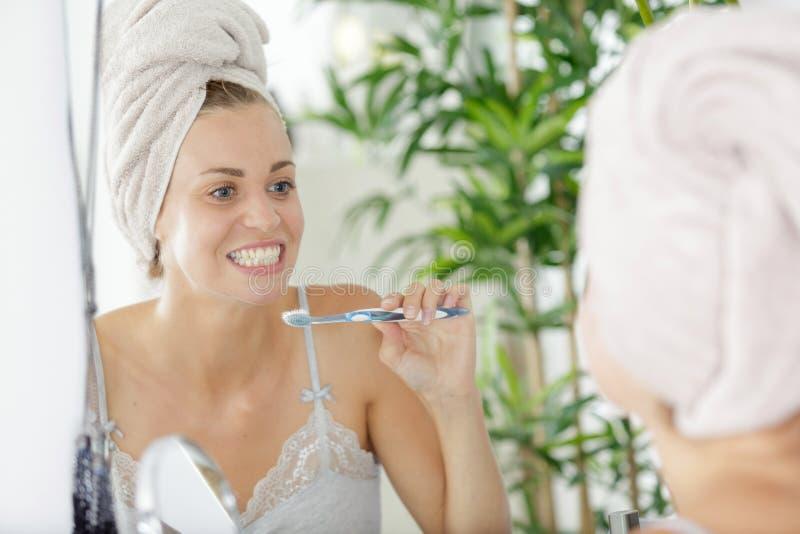Женщина чистя ее зубы щеткой стоковое фото