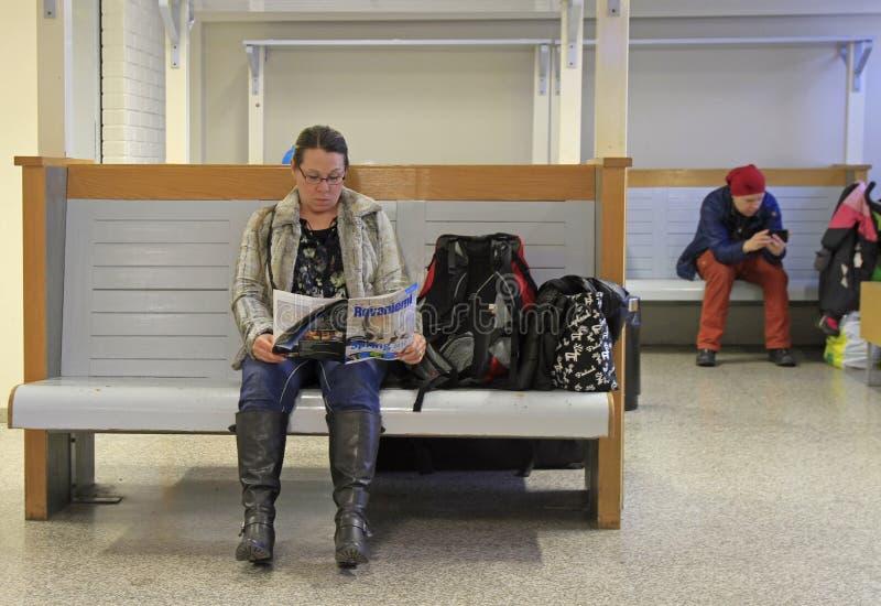 Женщина читает кассету на железнодорожной станции Rovaniemi стоковая фотография rf