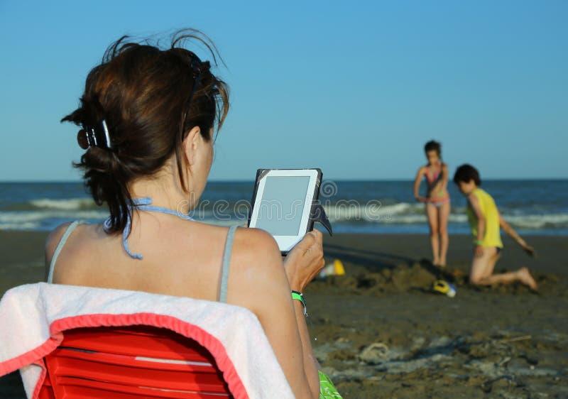 Женщина читает ebook на пляже в лете стоковая фотография rf