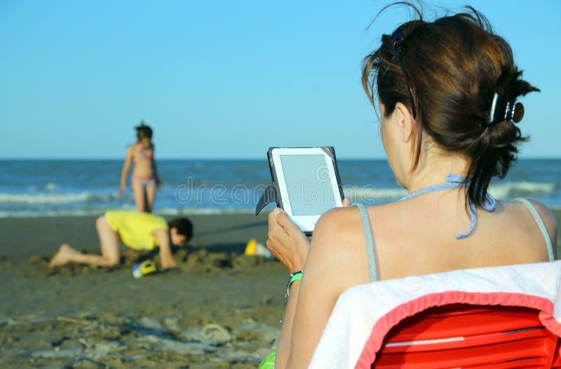 Женщина читает ebook на пляже пока ее играть детей стоковое изображение
